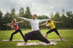 Formation en parc - l'instructeur montre l'exercice de flexibilité pour le groupe de filles dans le parc Photographie stock