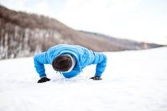 Formation extérieure avec l'athlète faisant des pousées sur la neige images libres de droits