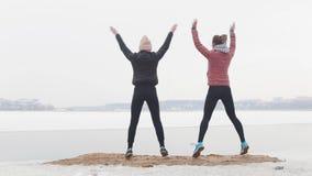 Formation extérieure Deux femmes minces se tenant sur la plage et sauter neigeux photographie stock