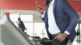 Formation masculine afro-américaine sérieuse sur le tapis roulant et parler au téléphone portable banque de vidéos