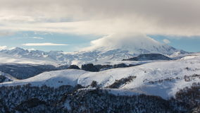 The formation and movement of clouds above the volcano Elbrus in the Caucasus Mountains in winter. stock footage