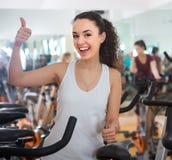 Formation positive de jeune femme sur des vélos d'exercice Photo stock