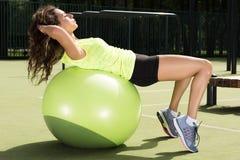 Formation sur la boule d'ajustement La jeune femme faisant des sports s'exerce sur la boule pour la formation images libres de droits