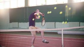 Formation sur le court de tennis Le jeune homme étant prêt pour le jeu mais lui obtient dispersé par des balles de tennis clips vidéos