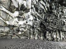 Formations de roche de basalte sur la plage noire de Reynisfjara, Islande, scintillant avec l'humidité de la mer photo stock