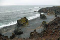 Formations de roche en plage noire de sable de Djupalonssandur photographie stock libre de droits