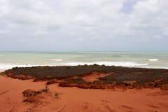 Formations de roche rouges antiques brillantes chez James Price Point, Broome, Australie occidentale du nord un jour nuageux d'ét Photo libre de droits