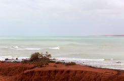Formations de roche rouges antiques chez James Price Point, Broome, Australie occidentale du nord un jour nuageux d'été Photos stock