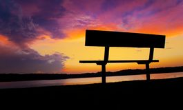 Formations spectaculaires rares de nuage pendant le coucher du soleil au-dessus des eaux calmes de lac et du banc de détente image libre de droits