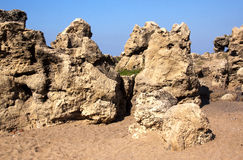 Formations of Weathered Rock Against Blue Sky on Beach Royalty Free Stock Photo