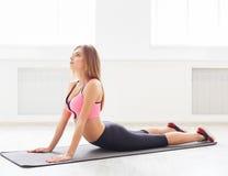 Formazione d'allungamento posteriore della donna di forma fisica all'interno Immagine Stock Libera da Diritti