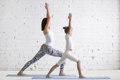 Formazione degli insegnanti di yoga dei bambini con il bambino della ragazza una posa di Virabhadrasana Immagini Stock