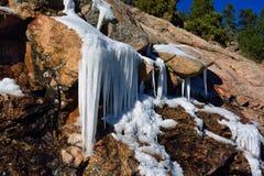 Formazione del ghiacciolo di inverno sulle rocce nelle montagne su Sunny Day Immagini Stock