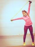Formazione della donna all'aperto con la corda di salto il giorno freddo Immagini Stock