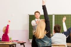 Formazione - insegnante con la pupilla nell'insegnamento del banco Fotografie Stock