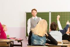 Formazione - insegnante con la pupilla nell'insegnamento del banco Immagine Stock Libera da Diritti