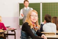Formazione - insegnante con le pupille nell'insegnamento del banco Fotografia Stock