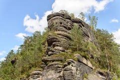 Formazione rocciosa alta coperta di alberi verdi in varie parti Fotografia Stock Libera da Diritti