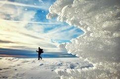 Formazioni di ghiaccio al tramonto, siluetta dello sciatore campestre in dist Immagini Stock Libere da Diritti