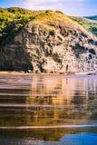Formazioni rocciose spettacolari riflesse in onde di marea delicate che investono la riva fotografia stock