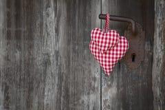 Forme à carreaux rouge du coeur deux accrochant sur la poignée de porte rouillée pour v Photos stock