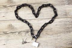 Forme à chaînes de coeur avec la serrure ouverte sur le backround en bois photos libres de droits