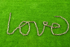 Forme à chaînes le mot AMOUR sur l'herbe Images libres de droits