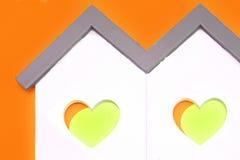 Forme à la maison blanche avec la fenêtre de forme de coeur de jaune orange Image libre de droits