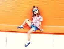 Forme óculos de sol vestindo da criança à moda da menina e a camisa quadriculado na cidade Fotos de Stock Royalty Free