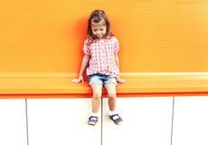 Forme óculos de sol vestindo da criança da menina e a camisa quadriculado sobre o fundo alaranjado Foto de Stock
