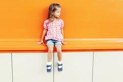 Forme óculos de sol vestindo da criança da menina e a camisa quadriculado sobre o fundo colorido Fotos de Stock