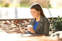 Forme adolescente usando un teléfono en una cafetería Foto de archivo