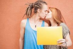 Forme a adolescentes os pares que beijam e que guardam o quadro no fundo vermelho Imagens de Stock Royalty Free
