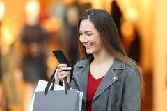 Forme al comprador que usa un teléfono elegante en una alameda Foto de archivo libre de regalías