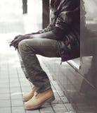 Forme al hombre africano en chaqueta negra, vaqueros y sentarse de las botas Fotografía de archivo libre de regalías