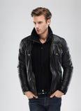 Forme al hombre, chaqueta de cuero del modelo, fondo gris Foto de archivo