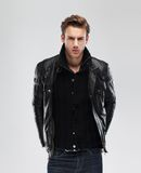 Forme al hombre, chaqueta de cuero del modelo, fondo gris Foto de archivo libre de regalías