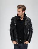 Forme al hombre, chaqueta de cuero del modelo, fondo gris Fotos de archivo libres de regalías