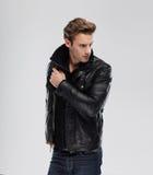 Forme al hombre, chaqueta de cuero del modelo, fondo gris Imágenes de archivo libres de regalías