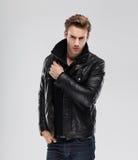 Forme al hombre, chaqueta de cuero del modelo, fondo gris Fotos de archivo