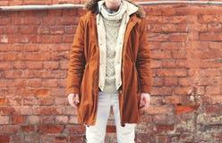 Forme al hombre en la chaqueta marrón caliente que presenta en una pared de ladrillo texturizada Fotografía de archivo