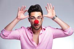 Forme al hombre joven con la nariz roja que actúa loco Fotos de archivo