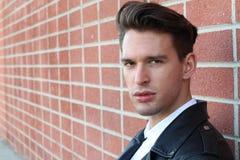 Forme al hombre joven en la camisa blanca y la chaqueta de cuero negra sobre la pared de ladrillo borrosa moderna con el espacio  foto de archivo