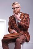 Forme al hombre que se sienta y que juega con su barba Foto de archivo