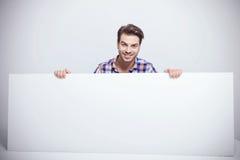 Forme al hombre que sonríe mientras que sostiene una cartelera blanca grande Fotos de archivo