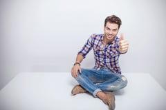 Forme al hombre que sonríe y que muestra los pulgares encima del gesto Foto de archivo libre de regalías
