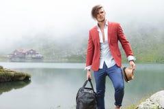 Forme al hombre que sostiene su bolso del sombrero y del viaje cerca del lago Imágenes de archivo libres de regalías