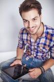Forme al hombre que sostiene un ordenador del cojín de la tableta mientras que sonríe Fotos de archivo libres de regalías