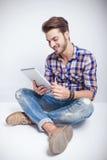 Forme al hombre que sostiene y que mira un ordenador del cojín de la tableta Fotos de archivo libres de regalías