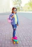 Forme al niño de la niña con las gafas de sol que llevan del monopatín y camisa a cuadros y mochila Foto de archivo